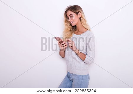 A girl in chatting on her smartphone.  A girl is looking for something at her phone.