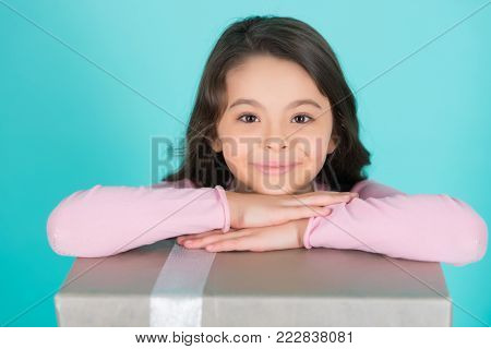 Birthday, new year, christmas, xmas, valentines day, anniversary, holidays celebration. Girl smile with hands on present box on blue background. Boxing day concept.