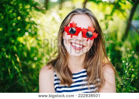 Portrait of funny beautiful white Caucasian young girl wearing canadian leaves sunglasses having fun outside. Happy white blonde woman celebrating Canada Day in summer park