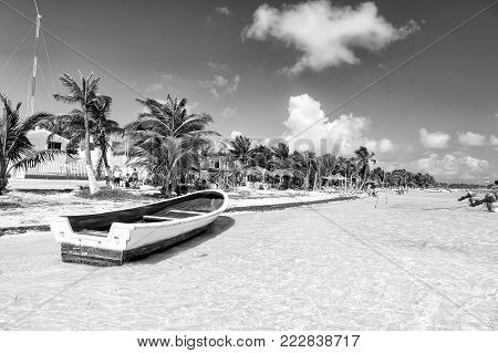 Mexico, Costa Maya - February 1, 2016: boat at tropical beach on clear sea or ocean water, white sand with green palms, tourist resort with people and straw umbrellas on sunny summer sky