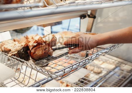Closeup macro shot of waitress barista taking muffin pastry with tongs from show window. Person at work place small business concept