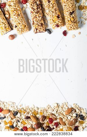 Granola bar. Healthy sweet dessert snack. Cereal granola bar with nuts, fruit and berries on a white stone table. Top view copy space. Vertical.