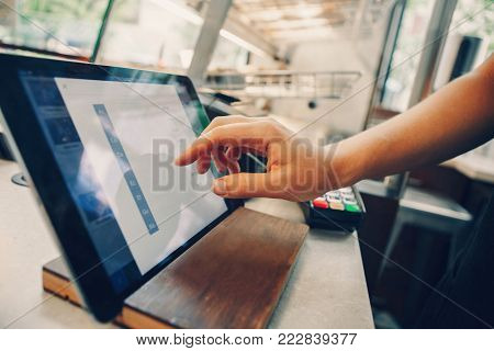 Closeup shot of caucasian cashier hands. Seller using touch pad for accepting client customer payment. Small business of coffee shop cafeteria.