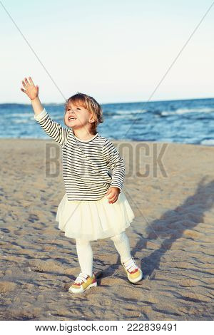 Portrait of one funny crying screaming white Caucasian child kid baby in striped shirt on ocean sea beach at sunset outdoors. Happy lifestyle childhood concept. Little girl lost something