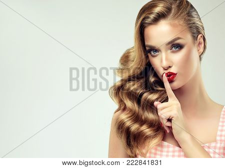 Shhhhh . Beautiful girl with bright makeup and curly hair telling a secret .Portrait  happy woman who is calling to someone .Funny girl model  whispering about something. Expressive facial expressions