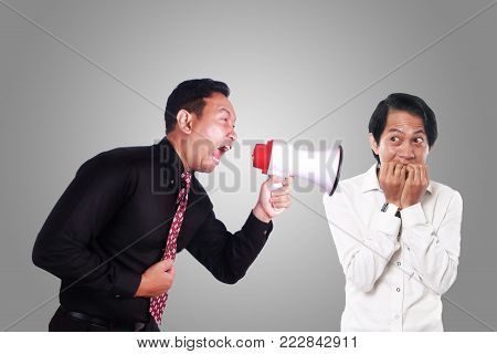 Portrait of angry boss manager businessman yelling screaming to his worker with megaphone