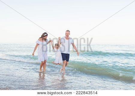 Dad, mom and daughter are walking along the beach. Dad and Mom raised daughter by the hand above the water