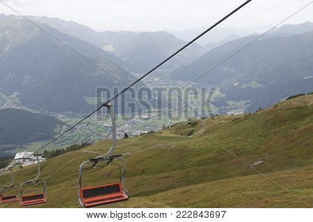 Chairlift ski lift in european Alps. Transporting hikers in summer season