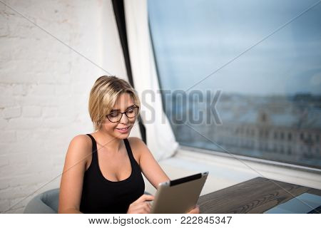 Smiling female manager in glasses reading e-book in internet via portable touch pad, sitting at work table near office window with copy space. Businesswoman searching information on digital tablet