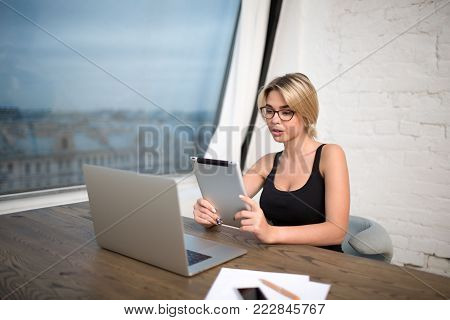 Young woman commercial real estate analyst reading e-mail on touch pad, sitting at the wooden table with laptop computer. Female secretary big successful company using digital tablet and net-book