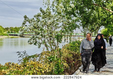 Isfahan, Iran - April 24, 2017: A mature Iranian couple walks along the embankment of the city river.