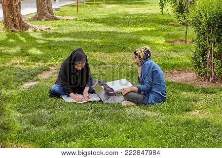 Isfahan, Iran - April 24, 2017: Two Muslim female students, dressed in Islamic hijab, are preparing for the exams, sitting on the lawn in the city park, using a laptop.