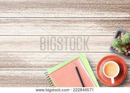 Wood office desk table with notebook,pencil,cactus flower and cup of coffee flat lay. Top view with copy space (selective focus). Office desk table concept.