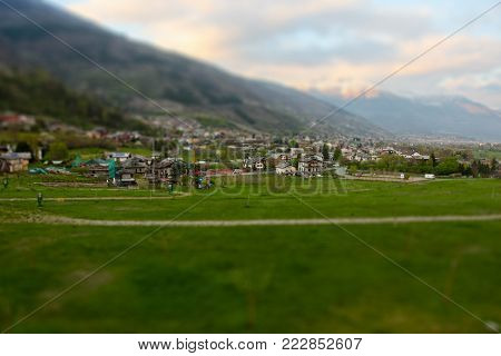 The Italian Alps, the valley in the suburbs of Aosta on the horizon of the mountain with snowy peaks, are blurry background. Tilt Shift Effect