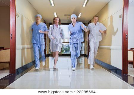 Team of surgeon and nurse running in hallway of hospital
