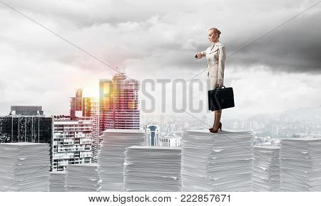 Confident business woman in suit standing on pile of documents and looking at watch with cityscape and sunlight on background. Mixed media.