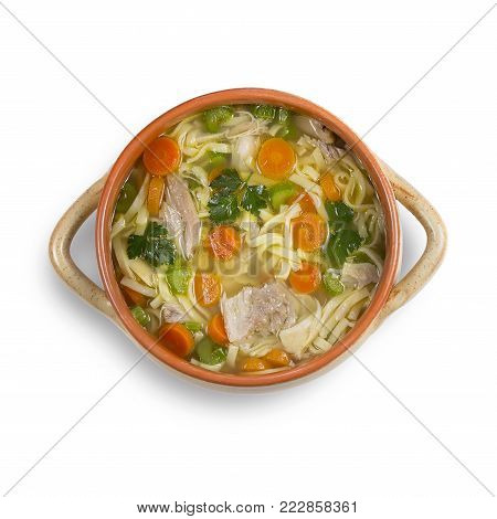 Chicken soup with noodles and vegetables on white background. High-angle shot. Close up.