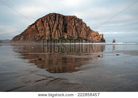 Morro Rock reflecting in water at Sunrise at Morro Bay State Park popular vacation / camping spot on the Central California Coast USA