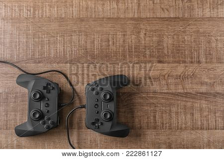 Video game controllers on wooden background