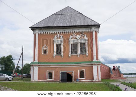 Vintage facade of a brick dand wooden two-storey house in traditional Russian style. Front view colse up