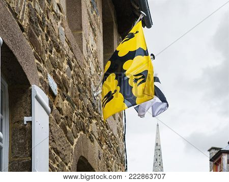 travel to France - yellow St Ivo's (Saint-Yves) flag of Tregor province and white Breton flags on wall of urban house in Treguier town in the Cotes-d'Armor department of Brittany in summer rainy day
