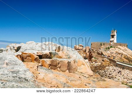 travel to France - view of pink rocks and Paon Lighthouse (Phare du Paon) on granite coast of Ile-de-Brehat island in Cotes-d'Armor department of Brittany in summer sunny day