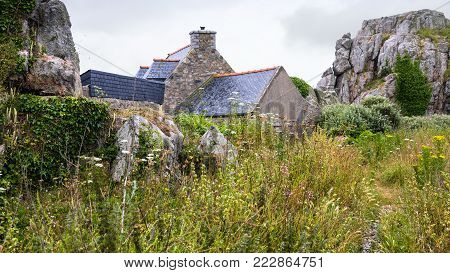 travel in France - typical Breton stone house and rocks in Plougrescant town of the Cotes-d'Armor department in Brittany in rainy summer day