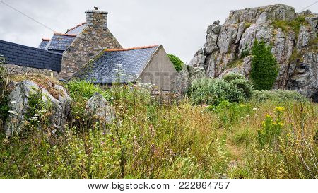 travel in France - traditional Breton stone house and rocks in Plougrescant town of the Cotes-d'Armor department in Brittany in rainy summer day