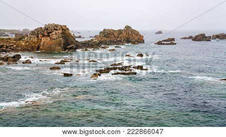 travel in France - view of rocky coastline of Gouffre gulf of English Channel near Plougrescant town of the Cotes-d'Armor department in Brittany in summer rainy day