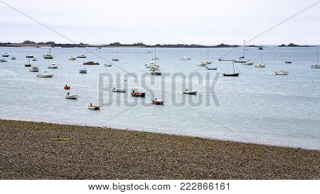 travel to France- many boats moored near pebble beach Plage de la Baie de Launay in Ploubazlanec commune in the Cotes-d'Armor department in Brittany in summer evening