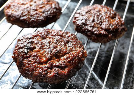 Burger patties on grill, closeup
