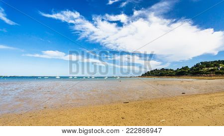 travel to France - view of sand beach Plage de la Baie de Launay on bay Anse de Launay of English Channel in Paimpol region of Cotes-d'Armor department of Brittany under blue sky in sunny summer day