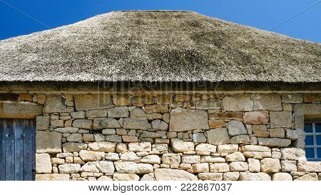travel to France - stone wall and thatched roof of old country house in Brehat commune at Ile-de-Brehat island in Cotes-d'Armor department of Brittany in summer sunny day