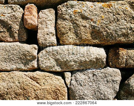 travel to France - stone wall from pink granite boulders of old country house in Brehat commune at Ile-de-Brehat island in Cotes-d'Armor department of Brittany in summer sunny day