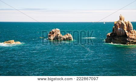 travel to France - granite rocks in ocean on shore of Ile-de-Brehat island in Cotes-d'Armor department of Brittany in summer sunny day