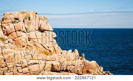 travel to France - pink granite cliff of Ile-de-Brehat island in Cotes-d'Armor department of Brittany in summer sunny day