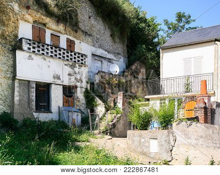 travel to France - old urban cave houses in rock on street Rue Victor Hugo in Amboise town in Val de Loire region in sunny summer day