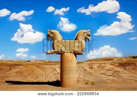 Stone column sculpture of a Griffin in Persepolis against a blue sky with clouds. The Victory symbol of the ancient Achaemenid Kingdom. Iran. Persia. Shiraz.