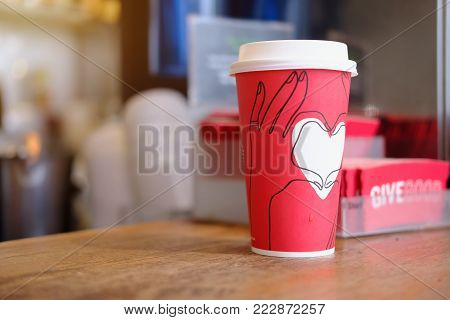 HONG KONG, CHAINA DEC 10 2017 : A Venti  Starbucks cup of coffee with STARBUCKS NEW GIVE GOOD RED HOLIDAY CUPS 2017 in starbucks offee shop. Starbucks is the world's largest coffee house with over 20,000 stores in 61 countries.