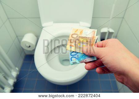 man discarding many euro  money in toilet