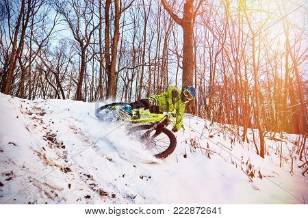 Moscow, Russia - January 2018: Winter cycling. Extreme riding on a mtb, mountain bicycle in the snow in the winter forest. Athlete on bicycle at winter. Jump and fly on mountain bike. MTB cycling.