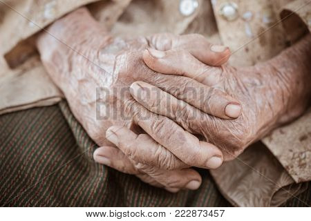 Hands Asian elderly woman grasps her hand on lap, pair of elderly wrinkled hands in prayer sitting alone in his house, World Kindness older and Adult care,  Mother day people concept poster