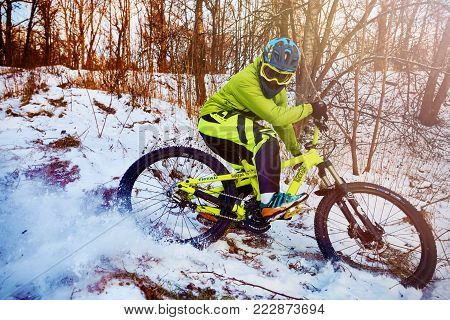 Moscow, Russia - January 2018: Winter cycling. Extreme riding on a mtb, mountain bicycle in the snow in the winter forest. Athlete on bicycle at winter. MTB cycling.