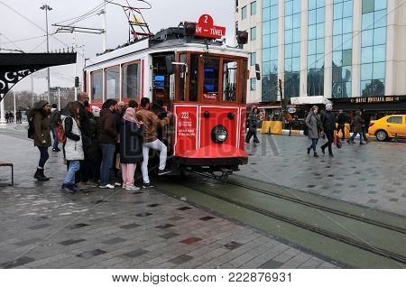 ISTANBUL, TURKEY - JANUARY 14, 2018: Passengers get on retro tramway in Taxim square