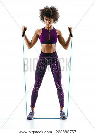 Fitness girl performs exercises with resistance band. Photo of girl with beautiful athletic body isolated on white background. Strength and motivation