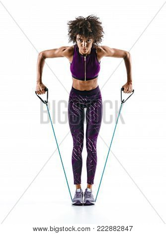 Sportswoman performs exercises with resistance band isolated on white background. Strength and motivation.