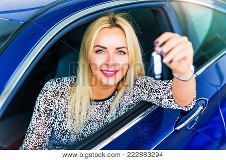 Happy young woman driver holding auto keys in her new modern luxury car