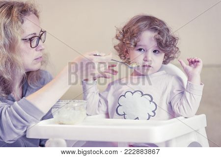 Mother feeds the baby with a spoon. The two-year-old child is naughty and refuses to eat.