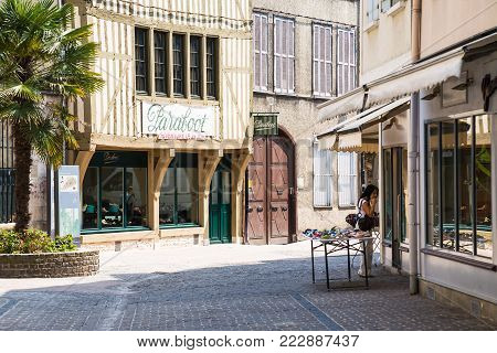 TROYES, FRANCE - JUNE 29, 2010: people near shop in old half-timbered houses on Rue General Saussier in Troyes city. Troyes is the capital of the Aube department in Champagne region of Northern France