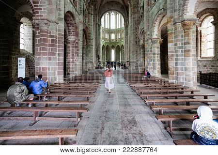 LE MONT SAINT-MICHEL - JULY 5, 2010: tourists in nave of Saint Michael's Abbey. Le Mont Saint-Michel is an island commune in Normandy, first monastic on the mount was built in the 8th century
